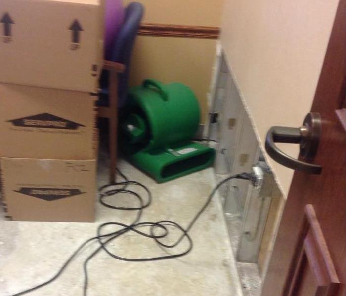 Removed flooring and dry wall with green drying equipment up and running next to cardboard SERVPRO boxes.