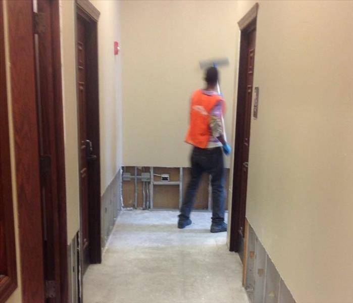 A SERVPRO crew member in an orange west standing at the end of a commercial hallway with flood cuts cleaning the walls.